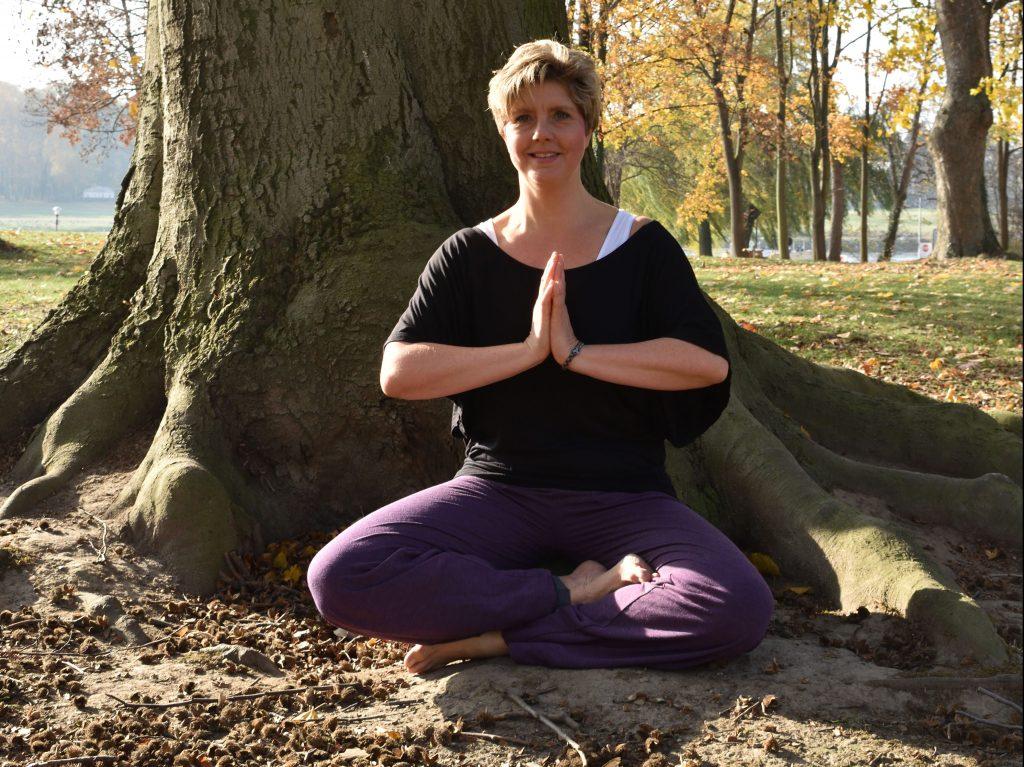 Mein Name ist Claudia Gründer und ich sitze im Yoga Schneidersitz vor einem großen Baum.
