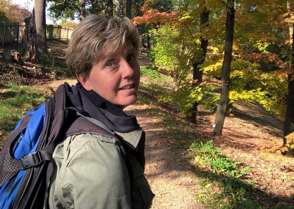 Mein Name ist Claudia Gründer und ich schaue beim Laufen auf einen herbstliche Waldweg über die Schultern und lächle.